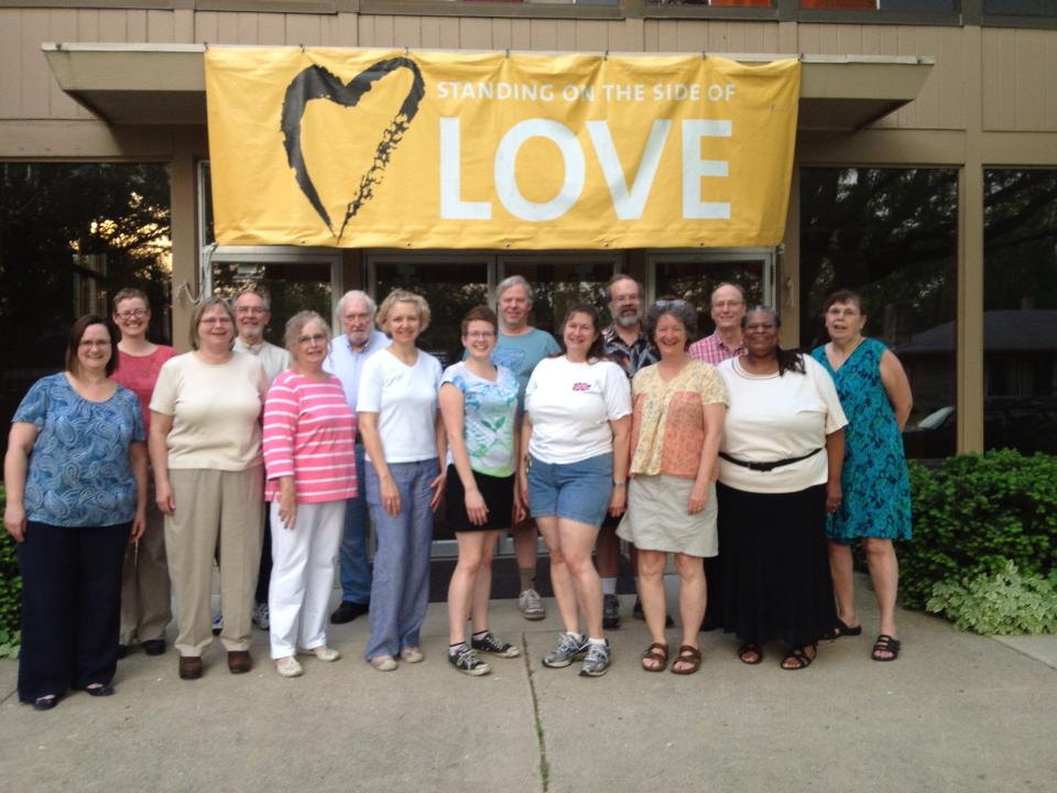 Church members in front of Standing on the side of love banner